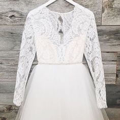 The Paloma gown by Elizabeth Dye is an ivory long sleeved wedding dress with a lace top and full tulle skirt.