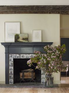 large vase of flowers in front of fireplace