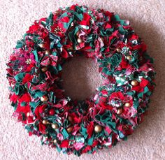 "Christmas wreath made from folded 2"" squares of fabric pushed into a polystyrene ring and a few glitzy bits added"