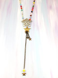"""""""Day Is Coming"""" - 1950's rhinestone star brooch paired with antique brass star Fringe on rainbow glass beaded chain hand crafted in Madagascar"""