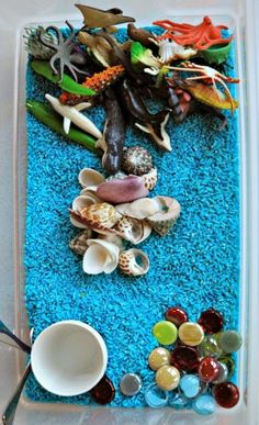 Blue rice ocean sensory bin, including sea glass, shells, and plastic ocean animals.