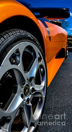 A Low Angle Driver Side View Front To Back On A Pearl Orange Lamborghini  Murcielago.