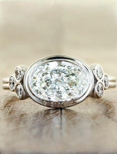 The Emmanuelle features a glorious oval diamond nestled in between 0.24tcw of six brilliant round white diamonds in a white gold band.