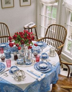 The breakfast room table is set with Anne Miller's collection of English blue-and-white china and antique cranberry glass. Antique Windsor chairs and oak stool were found in London. Wallpaper is Colbrooke Sprig by Cowtan & Tout.   - HouseBeautiful.com: