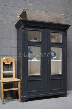 Vitrinekast 10096 - Origineel oude vitrinekast met een zwart grijze kleur. De kast heeft een prachtige uitgewerkte koof en sierlijke lijsten naast de deuren. De deuren hebben een speelse vakverdeling, achter de deuren zitten drie vaste legplanken.