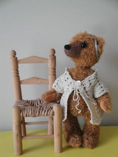 Lucy is a 22 cm/8.6 inch handmade bear. She has a soft mohair fur and wears a beige hand knitted sweater and has a green ribbon with bow and flower