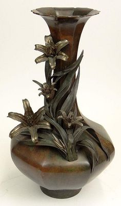 Large 20th Century Japanese Bronze Fluted Bottle Vase with Applied High Relief Lily Decoration. Unsigned. Good Condition or Better. Measures 22 Inches Tall and 12-1/2 Inches Wide.