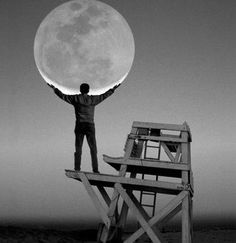 Beach photo holding the moon from lifeguard stand