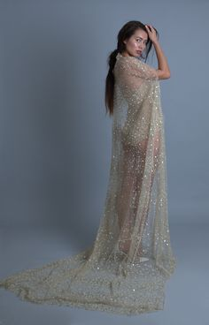 Astrea is a dramatic beaded cape gown. It can be ordered with or without a slip. On its own, it can be worn over anything. The champagne beaded net resembles a sky full of stars. This whimsical gown is perfect for an adventurous bride.