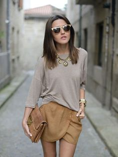 Shop this look on Lookastic:  https://lookastic.com/women/looks/oversized-sweater-shorts-clutch-sunglasses-necklace-bracelet/12346  — Gold Sunglasses  — Gold Necklace  — Grey Oversized Sweater  — Gold Bracelet  — Tan Leather Clutch  — Tan Shorts