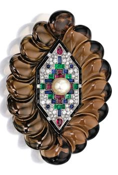 An Art Deco Platinum, Gold, Coloured Stone and Diamond Brooch, Suzanne Belperron, Circa 1938. The central hexagon-shaped plaque set with a pearl, accented by old European and single-cut diamonds, further decorated with rubies, sapphires, emeralds and onyx, within a fluted smokey quartz surround of later addition; circa 1938. #Belperron #ArtDeco #vintage #brooch