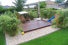Hollywoodschaukel aus Holz auf Holzdeck umgeben von Gartenbambus