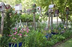 BIRDHOUSE GARDEN!  YES YES !!!    BIRDHOUSES tucked in and amongst the flowerbeds bordering the fence, both on the outside and inside.     Link to more of this house! soooo adorable and other ideas at the site!