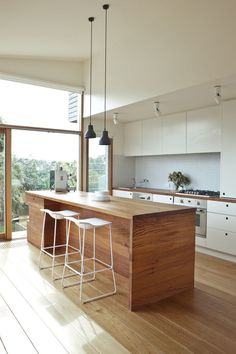Sleek and modern kitchen with clean lines, wood island, and minimal furniture