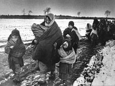 Russian villagers, primarily women and children, return to their village after the Germans have been pushed out, 1943. The village is most likely burned to the ground.