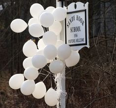 Balloons and flowers adorn the sign for Sandy Hook Elementary School on Saturday in Newtown, Conn.