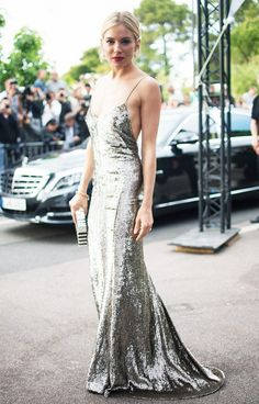 Sienna Miller stuns in a silver sequin floor-length slip dress paired with drop earrings, a box clutch, and a red lip