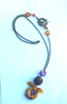 A gorgeous antique bronze necklace with a wire wrapped sari silk pendant and czech glass beads