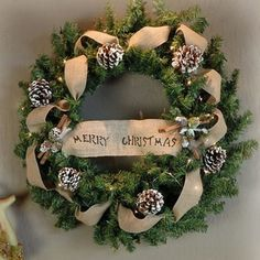 A burlap ribbon accented wreath mixes texture with tradition. #beverlys #Christmas #holidaydecor