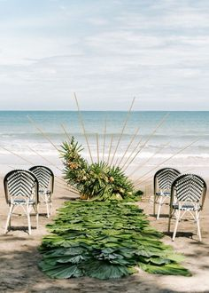 Beautiful beach ceremony with palm leaf aisle | Image by Raw Shoots Photography