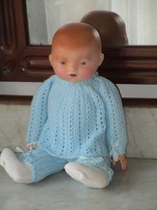 Antique Bebé with biscuit head (porcelain) and body of clothes with celluloid hands. This baby came with droopy eyes which have been glued together.