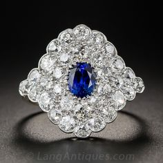 Edwardian Diamond & Sapphire Dinner Ring. Artfully handcrafted in platinum over gold, this stunning ultra-sparkler, dating from the beginning of the last century centers on a gorgeous and glistening true blue sapphire, weighing 1.03 carats. The lovely gemstone is enveloped within 2 carats of closely packed, high-color, European-cut diamonds arrayed in a gently curved lozenge shaped ring outlined with a scalloped border. 3/4 inch long and absolutely stunning. Circa 1910.