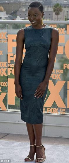 Ladies rule: Danai Gurira wowed the Comic Con crowd in a form-fitting grey-blue number while Emily Kinney bared her toned midriff in a confetti-patterned crop top and matching pencil skirt