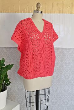 Vintage 1970's handknit sweater. All done in a vibrant, hot pink color. Simple cut in a loose, pull-over style is accented by a deep, v-neckline. Crocheted pattern is super feminine and the open weave                                                                                                                                                                                 More