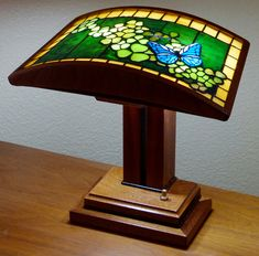 An art-glass desk lamp featuring butterflies in a bed of clover!  The base is African Mahogany and Wenge.  From Pandanus Designs!