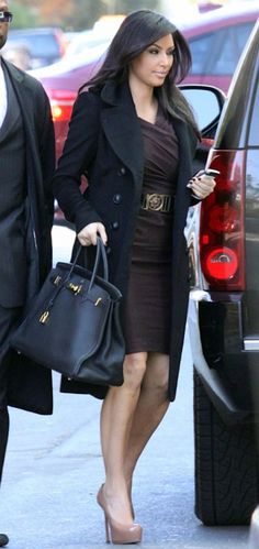 Kim Kardashian in Jacket and belt – Burberry    Dress – Donna Karan    Purse – Hermes    Shoes – Yves Saint Laurent