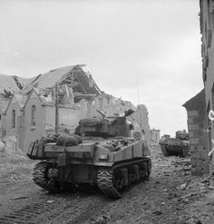 A Sherman and Churchill tank advance through Overloon during the attack by 3rd Division on an enemy pocket near the town, 14 October 1944.