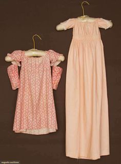 """Two Children's Calico Dresses, Early !9th century; 1st 1820s pink vertical print, drawstring waist and neckline, short sleeves with detachable long sleeves, W 24"""", L 25""""; 2nd tiny orange print baby's carriage dress, drawstring waist and neckline, W 21"""", L 42"""""""