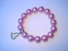 Pulseira perolada, na cor lilás/rosa, com pingente de coração prateado e fio de silicone.