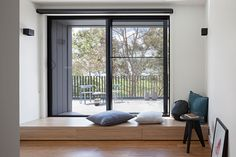 At the top of the stairs in this modern home is a small area with access to a balcony. A small wooden bench acts as a step and a quiet place to relax and look out to the park.