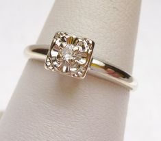 """A typical style of the 1960's. Very cute and petite! This is an illusion set solitaire. """"Illusion"""" stands for the way that the stone is set. Instead of just traditional 4 or 6 prongs, the diamond is set into a larger carved head to give a bigger impact - the """"illusion"""" of a larger stone. The diamond is a 0.05 carat (5 point) transitional cut, with VS clarity and H color. The head has 4 prongs, which are all in great shape. Ring is 14 karat white gold, weighs 1.8 grams and is size 6.5."""