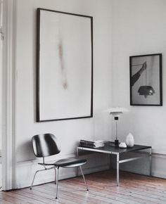 white walls. rustic floors. sleek chair and table.