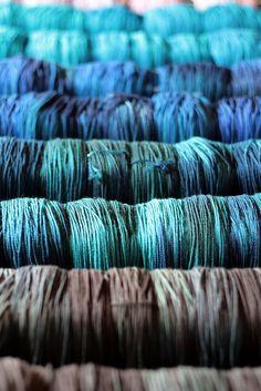 newly dyed Tanis Fiber Arts yarn drying on racks.
