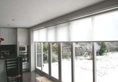 Roller blinds, in Hessian white fitted with Bifold Doors to reduce the intensity of the sun when lowered, but scarcely noticeable when fully raised