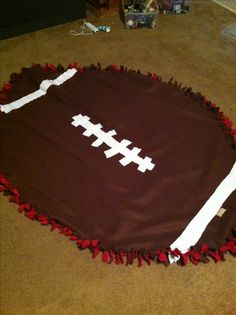 Football shaped tie blanket! A Rachel original ;) made with 2 yards of red and brown fabric, 1/2 a yard of white. sew the white on the brown before tying the knot then cut strips on the edges and tie a knot! perfect for snuggling up at a football game ;)