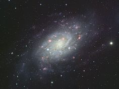 "Spiral Galaxy NGC 2403. The pink emission nebulae and blue reflection nebulae looks like a scattering of blossoms. The galaxy is located 14 million light years away in the constellation Camelopardalis. (Credit & Copyright: Suprime-Cam, Subaru Telescope, NAOJ) Mona Evans, ""What Is a Galaxy"" http://www.bellaonline.com/articles/art179279.asp"