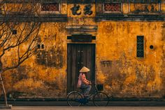 Date Taken:Apr 25, 2016  Date Uploaded:Apr 25, 2016  Location:Hoi An, Quang Nam, Vietnam  Camera:NIKON CORPORATION NIKON D810  Focal Length:175 mm  Shutter Speed:1/640 sec  Aperture:f/4  ISO:400  Early morning in Hoi An, as a cyclist passes one of the classical yellow painted buildings along the riverbank in the old town.