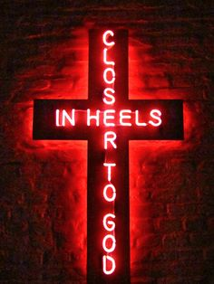 High heels. Closer to god. Neon religious kitsch.