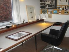 """Finn Juhl Kratvaenget House: Finn Juhl's office. There's an old leather briefcase standing on the floor, behind the chair. Posters advertising his own work and products hang on the bulletin board to the right. The drawing """"Two Pitchers"""" is by Juhl. He also designed the black leather office chair in 1965."""