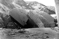 St. Francis Dam Flood March 12-13, 1928, Los Angeles County, California. Looking downstream to huge blocks of cement at the base of the east abutment of the dam. Note dust clouds in the background from landslides that were still in progress. March 17, 1928.