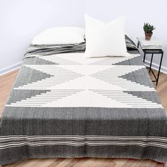 Bico Bed Blanket - Meet the zero-effort style statement. Featuring a bold Brazilian design and minimal color palette, this one-and-done blanket instantly ups the game of any bed.  Hand-loomed using the tapestry technique of interchanging vertical and horizontal threads, this all-cotton blanket takes a day to complete. Each one is crafted by a group of 6 weavers who live and work in the small town of São João del Rei.