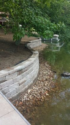 We tore out an old wooden reatining wall and replaced with a tumbled retaining wall block. We placed creek rock on the front side of the wall for a visual apperance and to also hide the concrete footing. We also extended the paver walkway, attached the dock, and added topsoil to freshen everything up. Located in central MO. ** www.greenacresmidmo.com ***
