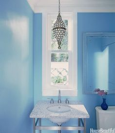 Paint makes the big statement here, giving a narrow space the depth of sea and sky. Designer Sally Markham chose a gloss finish to catch sunshine or lantern light. Click through for more ideas for bathroom colors and paint color schemes.