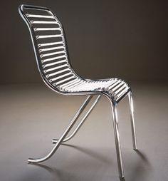 Chaise de Michel Dufet Ontwerp 1930 Materiaal: geraamte in gebogen ronde buizen in vernikkeld metaal. De elastieken veren zijn verkrijgbaar in zwart, wit, rood, geel en blauw