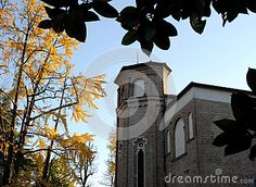 Photo made at the Scrovegni chapel with the blue sky background in Padua in the Veneto (Italy). Image made from the garden of the Hermits is seen framed by green leaves in the foreground and yellow leaves to the left and further away, the back of the small church where the fresco by Giotto.
