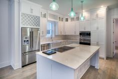 Traditional Kitchen with Glass panel, Kitchen island, Complex marble counters, Flat panel cabinets, L-shaped, Pendant light